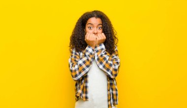 young pretty african american woman looking worried, anxious, stressed and afraid, biting fingernails and looking to lateral copy space against yellow wall