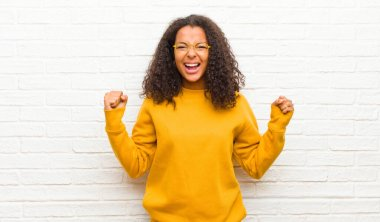 young black woman feeling happy, surprised and proud, shouting and celebrating success with a big smile against brick wall