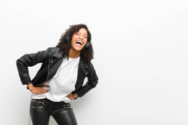 young pretty black woman listening music with a headphones wearing a leather jacket against white wall