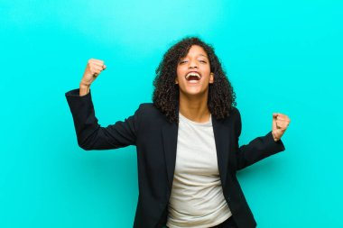 young black woman shouting triumphantly, looking like excited, happy and surprised winner, celebrating against blue wall