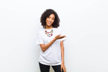 young cool african american woman smiling cheerfully, feeling happy and showing a concept in copy space with palm of hand
