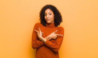 young pretty black woman looking puzzled and confused, insecure and pointing in opposite directions with doubts against orange wall