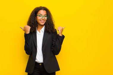 black business woman smiling joyfully and looking happy, feeling carefree and positive with both thumbs up against orange wall