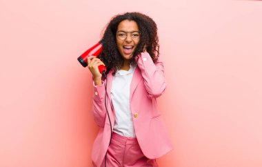 young black pretty woman with a hairdesser against pink wall background