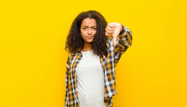 young pretty african american woman feeling cross, angry, annoyed, disappointed or displeased, showing thumbs down with a serious look against yellow wall