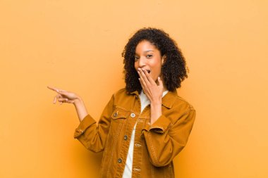 young pretty black woman feeling happy, shocked and surprised, covering mouth with hand and pointing to lateral copy space against orange wall