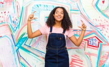 young pretty african american woman framing or outlining own smile with both hands, looking positive and happy, wellness concept against graffiti wall