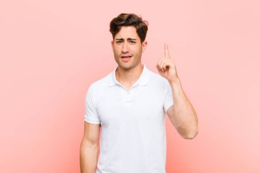 young handsome man feeling like a genius holding finger proudly up in the air after realizing a great idea, saying eureka against pink background