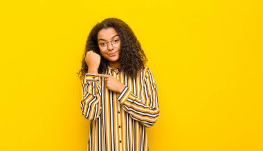 young pretty african american woman looking impatient and angry, pointing at watch, asking for punctuality, wants to be on time against yellow wall