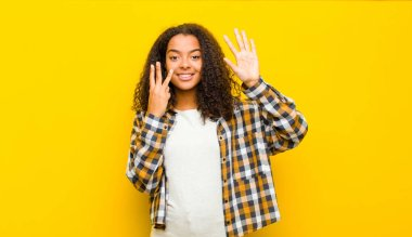 young pretty african american woman smiling and looking friendly, showing number eight or eighth with hand forward, counting down against yellow wall