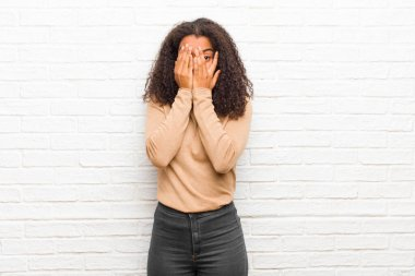 young black woman covering face with hands, peeking between fingers with surprised expression and looking to the side against brick wall