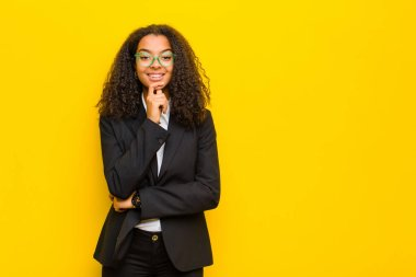 black business woman looking happy and smiling with hand on chin, wondering or asking a question, comparing options against orange wall