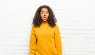 young black woman feeling shocked, happy, amazed and surprised, looking to the side with open mouth against brick wall
