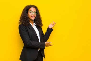 black business woman smiling proudly and confidently, feeling happy and satisfied and showing a concept on copy space against orange wall