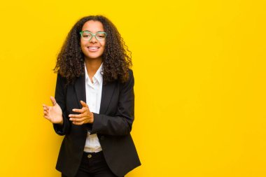 black business woman feeling happy and successful, smiling and clapping hands, saying congratulations with an applause against orange wall