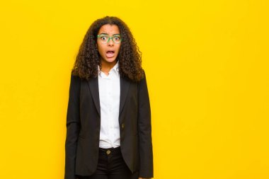 black business woman feeling terrified and shocked, with mouth wide open in surprise against orange wall