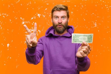 young blonde man with dollar bills or banknotes wearing a purple hoodie against damaged orange wall