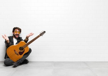 young musician man feeling happy, astonished, lucky and surprised, like saying omg seriously? Unbelievable with a guitar, rock and roll concept