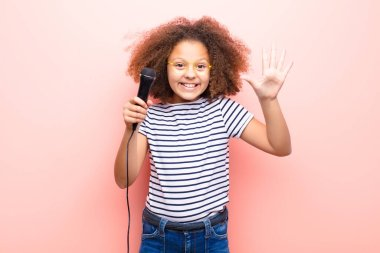 african american little girl  against flat wall with a microphone