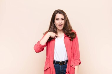 young pretty woman looking happy, proud and surprised, cheerfully pointing to self, feeling confident and lofty against beige background
