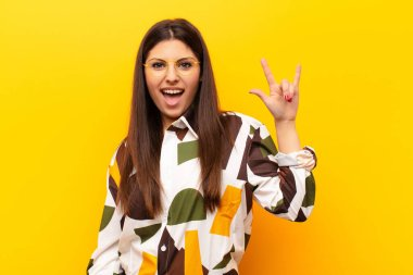 young pretty woman feeling happy, fun, confident, positive and rebellious, making rock or heavy metal sign with hand against yellow wall