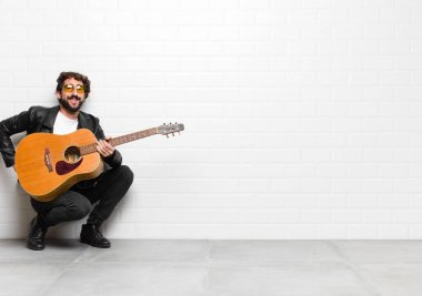 young musician man smiling happily with a hand on hip and confident, positive, proud and friendly attitude with a guitar, rock and roll concept