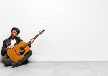 young musician man feeling puzzled and confused, with a dumb, stunned expression looking at something unexpected with a guitar, rock and roll concept