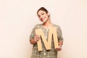 mladá hezká žena vzrušená, šťastná, radostná, drží písmeno M abecedy, aby vytvořila slovo nebo větu.