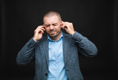 young businessman looking angry, stressed and annoyed, covering both ears to a deafening noise, sound or loud music against flat wall
