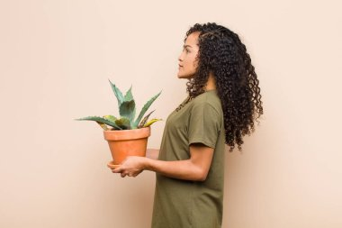 Young black woman on profile view looking to copy space ahead, thinking, imagining or daydreaming holding a cactus stock vector