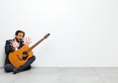 young man with guitar on floor in room