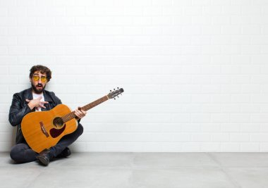 young man with guitar on brick wall background