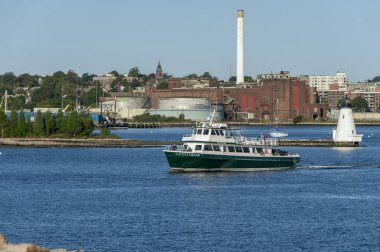 New Bedford, Massachusetts, USA - October 19, 2018: Cuttyhunk ferry crossing New Bedford inner harbor with lighthouse in background