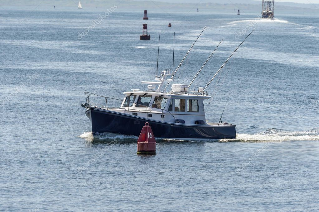 Recreational fishing boat passing buoy in New Bedford outer harb