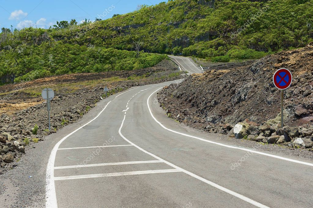 Curved asphalt road over the hot volcanic lava at Reunion island, France.