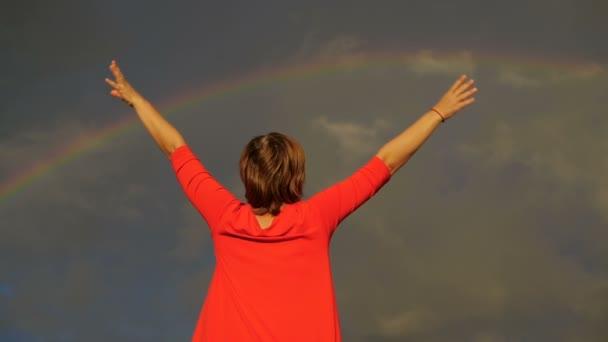 Vissza lövés a nő, hogy emelkedik a kezét az égre szivárvány Időjárás.
