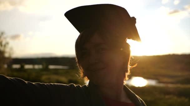 Sagoma di mezzo donna invecchiata che in piedi al tramonto in cappello studente.
