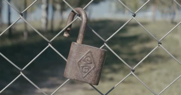 4k - kovový zámek, zavěšené na plotě na pozadí krásné krajiny