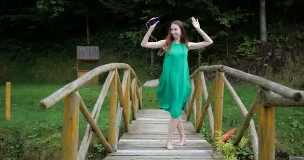 Sexy dívka v zelených šatech tančí s hearphones na dřevěný most - 4k