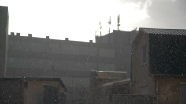 Rain over low buildings in slow motion