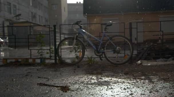 Jízdní kolo zaparkované poblíž plotu v deštivém počasí