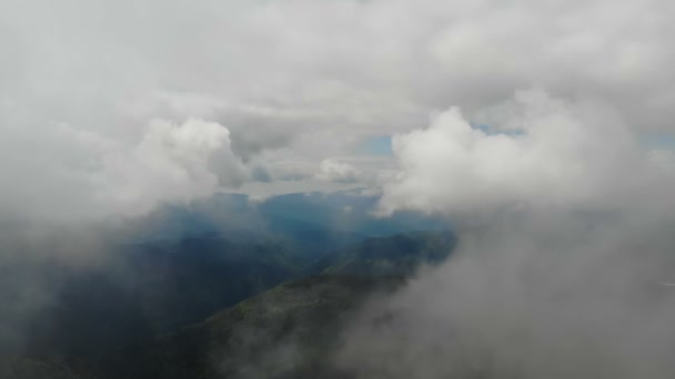 Aerial shot over mountains at sunny day with a lot of clouds into the sky.