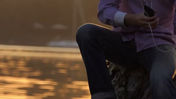 Happy man listens to the music and sits on a lake bank in slo-mo