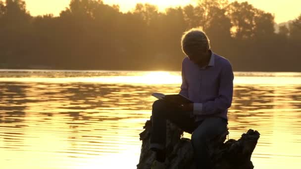 European man sits on a lake bank and reads a book in slo-mo