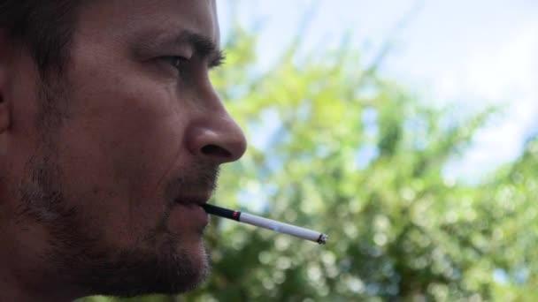 ein Mann mit ernstem Gesicht raucht in Zeitlupe.
