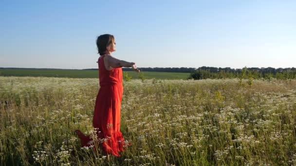 Krásná žena v červených šatech dělá dýchací cvičení v poli po-mo