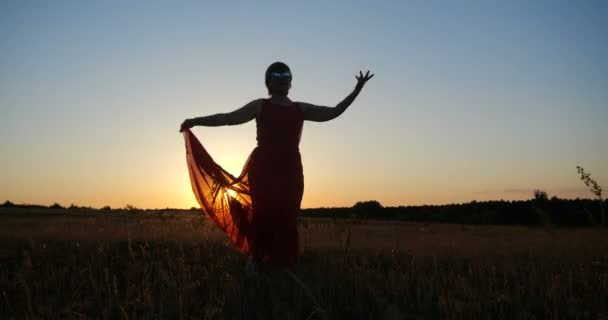 Inspired woman in a red dress dancing in a horizonless field at sunset