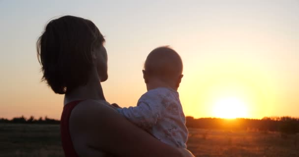 Romantic woman with a child in hands looking at sunset in a filed in slo-mo