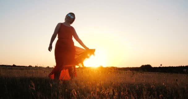 Happy stylish woman dancing and spinning in a large field at sunset in slo-mo