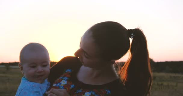 Smiling young mother and her kid enjoying life in a field at sunset in slo-mo